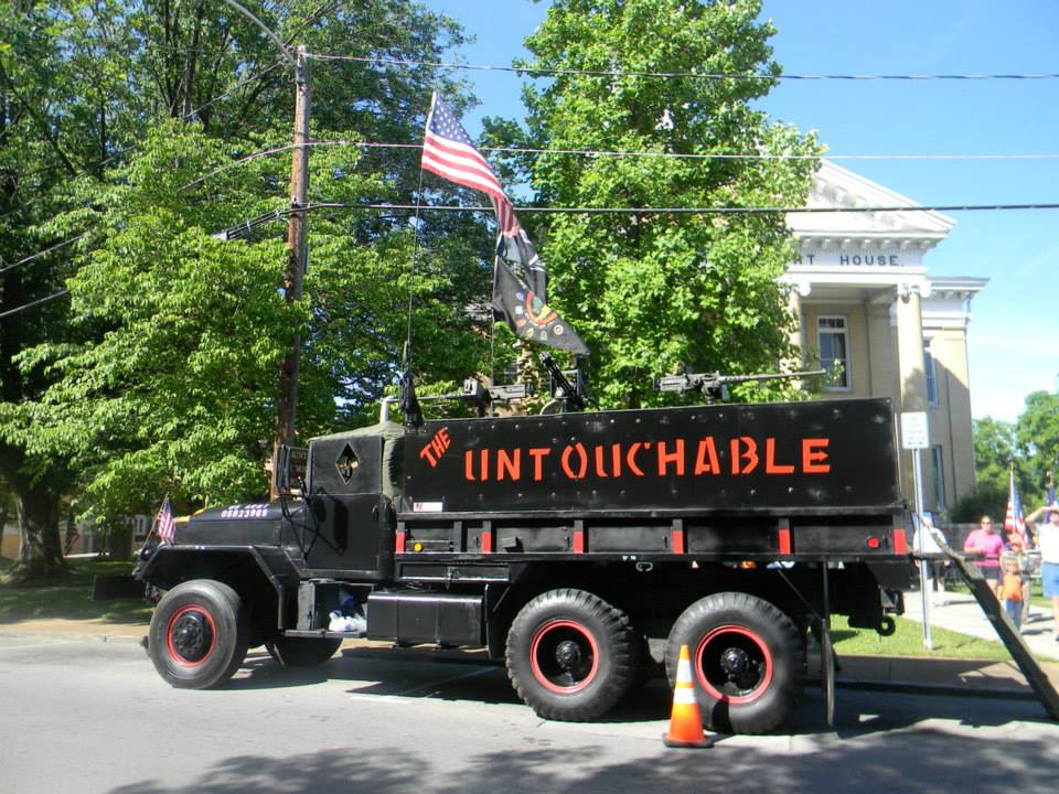 "Image of black tank like truck with orange writing ""the Untouchables"""